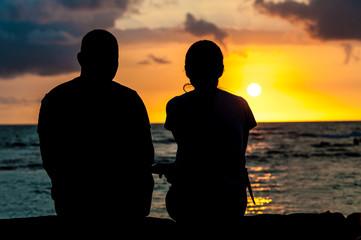 夕日を見つめるカップルのシルエット