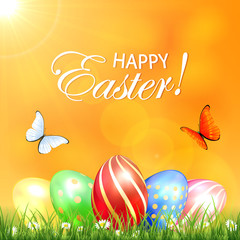 Butterflies and colored Easter eggs in a grass