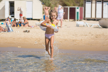 Happy girl running to swim in the sea