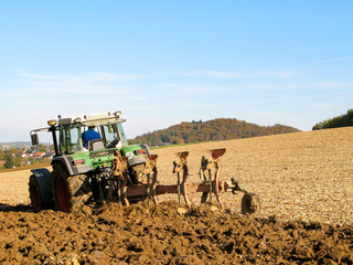 Green tractor cutting furrows on a brown acre in the Kraichgau, Germany