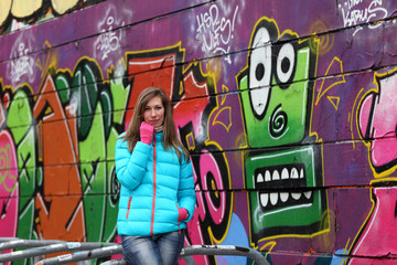 Beautiful blonde woman in jacket and blue jeans in front of a wall with graffiti