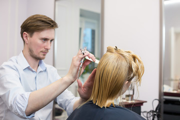 A hairdresser making a haircut for a blonde female client in hairdressing salon. Selective focus