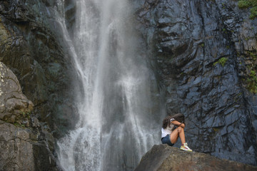 girl on rock with waterfall background