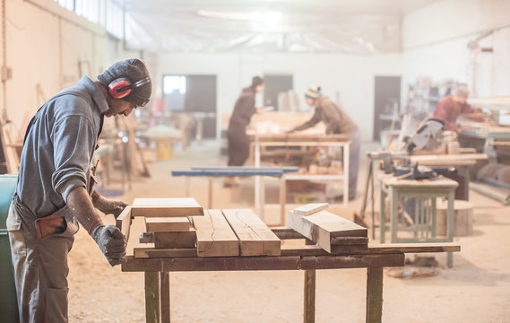 Man doing woodwork in carpentry / Carpenter work on wood plank in workshop