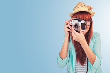Composite image of portrait of a smiling hipster woman holding a camera