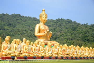 Big Golden and thousand of Golden Buddha statues with green moun
