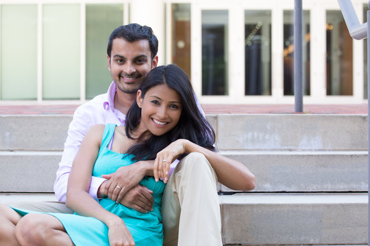 Closeup portrait, attractive wealthy successful couple in pink shirt and green dress holding each other smiling, isolated outside stairwell background.