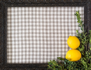 Lemons and branches of buxus on the background of checkered textile framed with a shabby black wooden frame