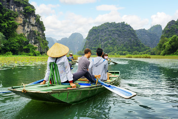 Tourists in boat. Rower using her feet to propel oars, Vietnam