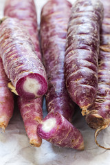 Purple carrots over white background