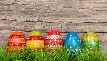 Colorful easter eggs in green grass over rustic wooden backgroun
