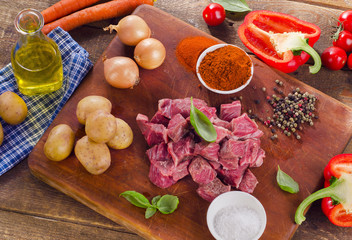 Ingredients for stew or goulash  on a old cutting board.