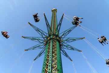 People Having Fun In Carousel Swing Ride At Amusement Park