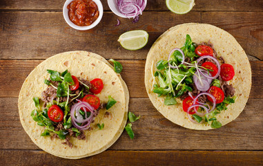 Two mexican tacos on a rustic wooden table.