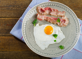 Fried egg with bacon for breakfast.