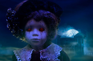 Old mystical scary horror doll looking with red demonic eyes with haunted horror house.