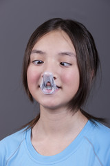 Girl looks at popped gum on her nose.