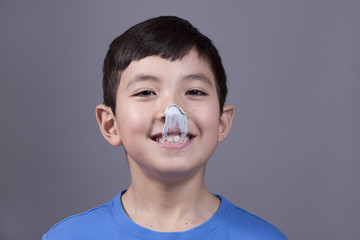 Boy smiles at gum on his nose.