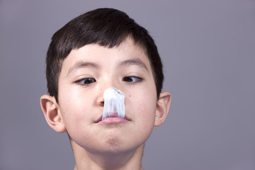 Boy looks at popped gum on his nose.