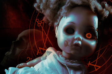 Possessed demonic horror doll with red pentacles, glowing eye & human skull on background.