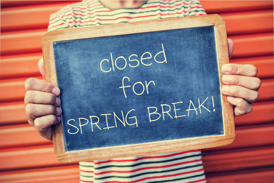 man and chalkboard with text closed for spring break
