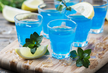 Blue curacao liqueur with lemon on the wooden table Wall mural