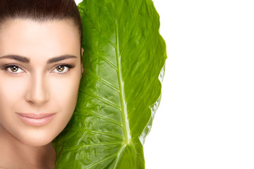 Beautiful spa girl with green leaf over white background