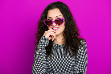 beautiful girl glamour portrait on magenta in heart shape sunglasses, long curly hair