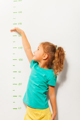 Little girl pretend how high she is on wall scale