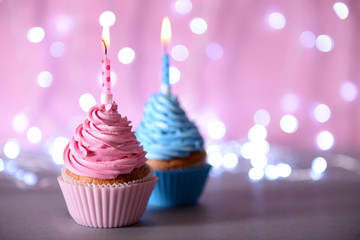 Two cupcakes with candle on a glitter background