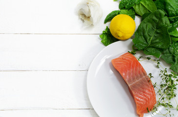 Raw salmon fillet with aromatic herbs, garlic, lemon and spinach