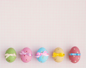 Vintage pastel easter eggs with ribbon over checkered background