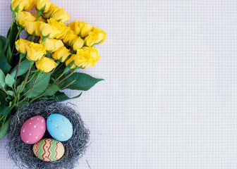 Vintage pastel easter eggs in nest and yellow flowers over checkered background