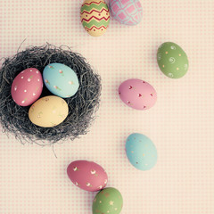 Vintage pastel easter eggs and nest over checkered background