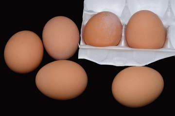 Half dozen brown eggs in styrofoam container