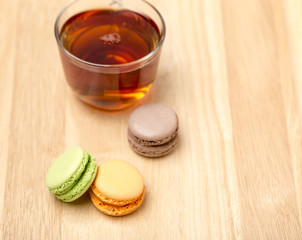 Glass cup of black tea and colorful macarons
