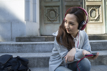 Women are listening to music with headphones sitting on the stairs of the park