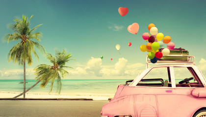 Vintage pink classic car with heart colorful balloon on beach blue sky - concept of love in summer and wedding. Honeymoon trip