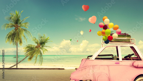 Wall mural Vintage pink classic car with heart colorful balloon on beach blue sky - concept of love in summer and wedding. Honeymoon trip