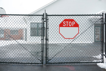 stop sign on iron chain link fence gate