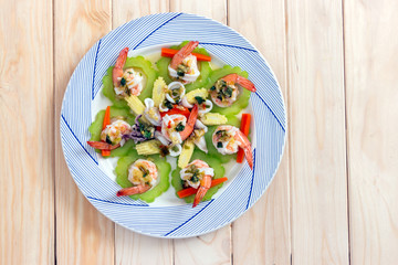 top view of boiled shrimp, squid and vegetable topping with spicy seafood sauce on wooden background
