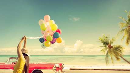 Wall Mural - Happy young woman holding colorful balloons with floating, concept of journey honeymoon in summer on tropical beach blue sky - vintage color tone