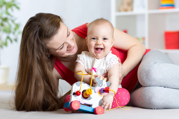 Mother and baby girl playing with toy in living room