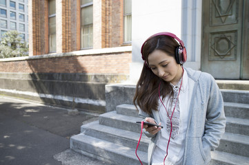 Asian women are listening to music with a headphone