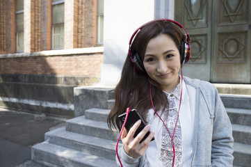 Beautiful Asian woman is listening to music with a headphone