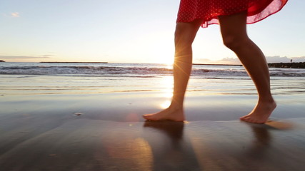 Wall Mural - Woman feet and legs walking on beach at sunset. Closeup of beautiful girl in summer dress against the sun flare.