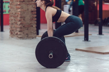 Sport girl doing exercise with barbell