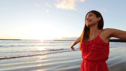 Wall Mural - Asian woman happy walking on beach at sunset cheerful and jumping full of joy. Fresh free girl enjoying summer beach in sundress during vacation holiday travel. Mixed race Asian Caucasian model.