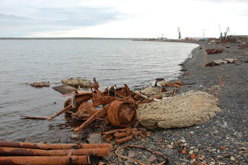 Old rusty abandoned metal vehicle parts at arctic sea coast