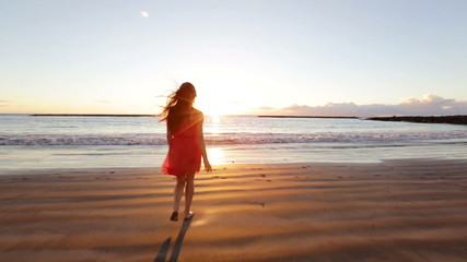 Wall Mural - Summer woman beach freedom happy concept. Young woman running towards ocean in dress at sunset with arms stretched free during holidays vacation travel. Beautiful free mixed race Asian Caucasian girl